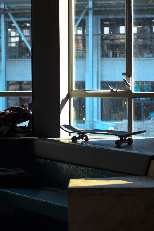 skateboard beside glass window