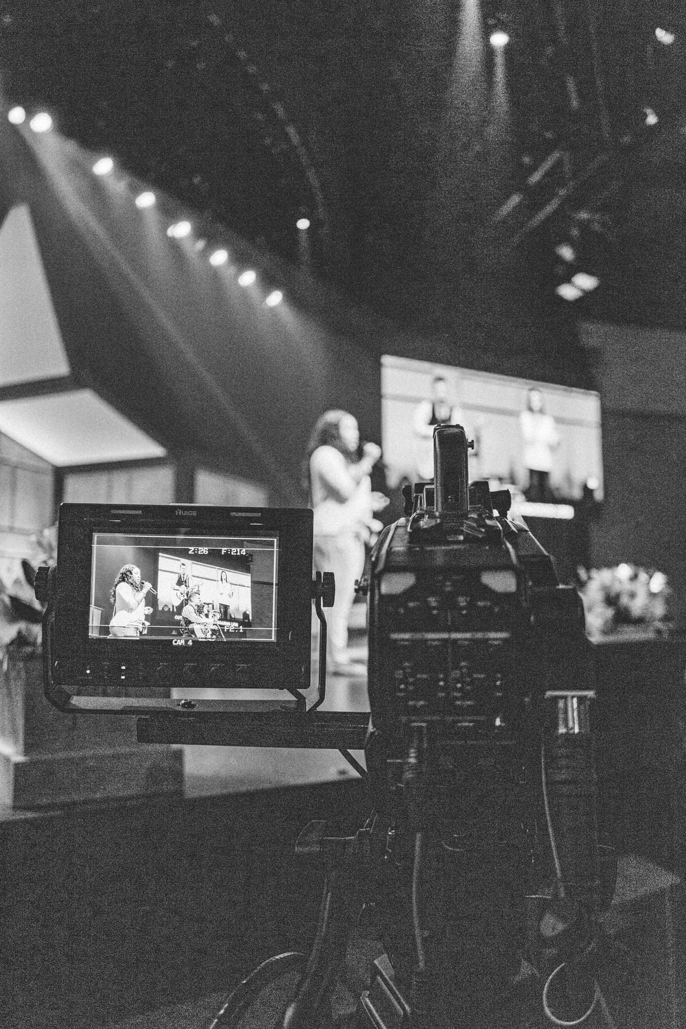 greyscale photography of video camera capturing person standing on stage