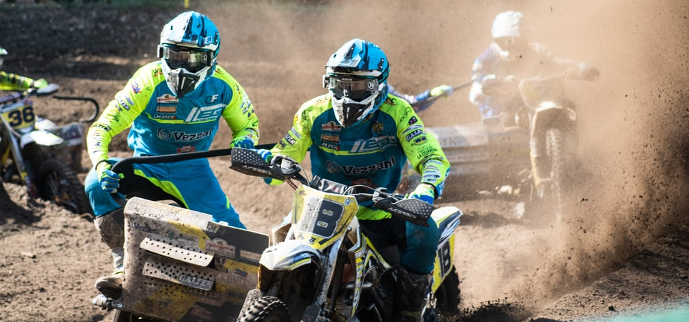 racers riding trike dirt bikes on dusty ground during daytime