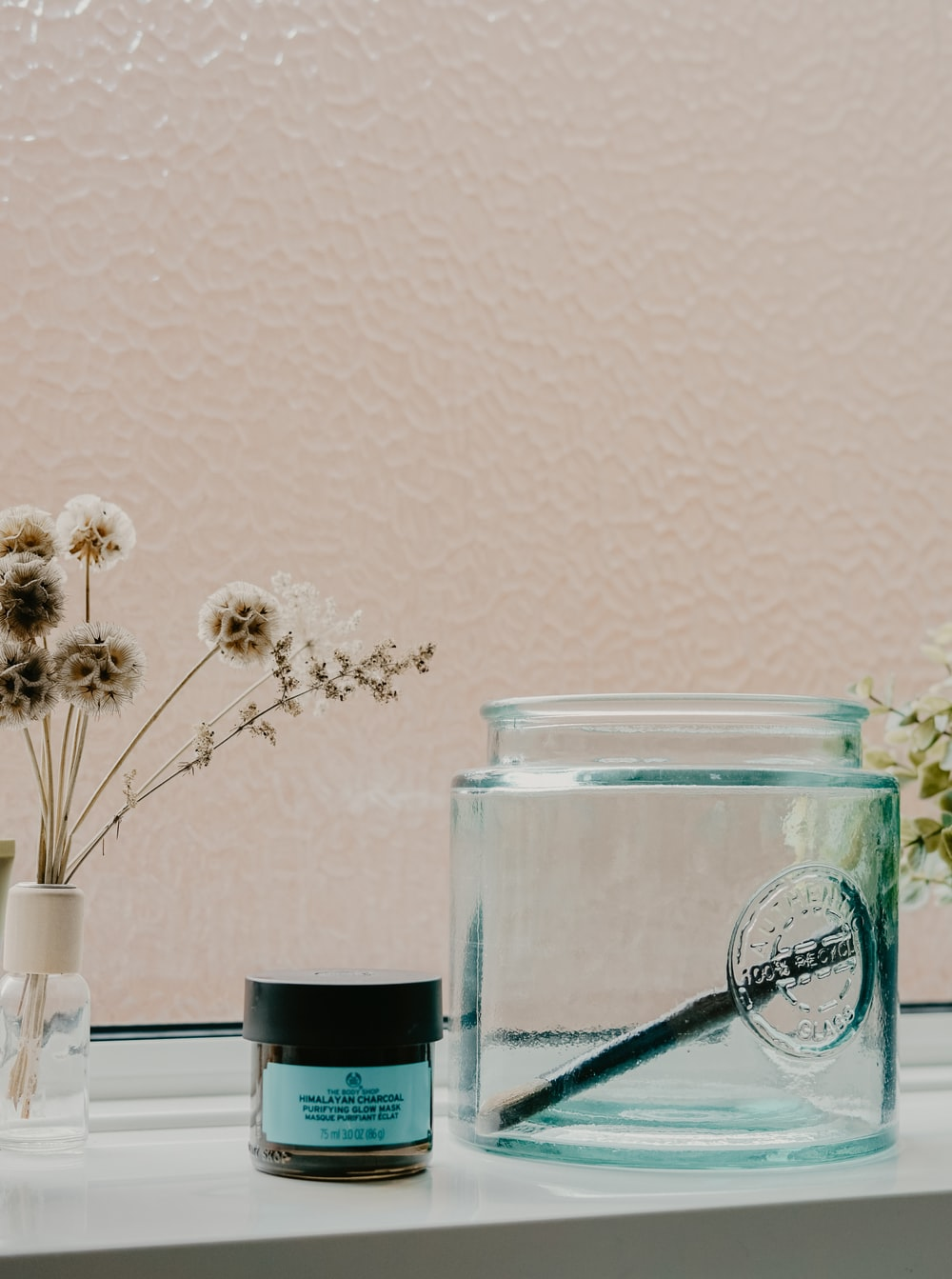 white and black labeled jar beside glass container