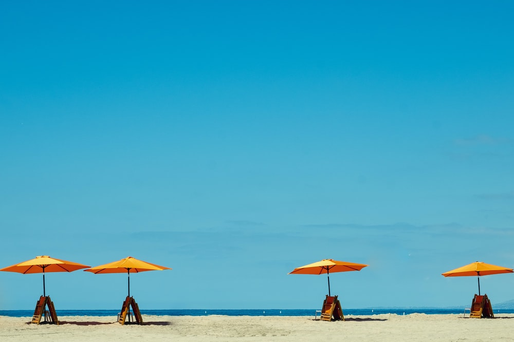 four yellow-and-orange parasols