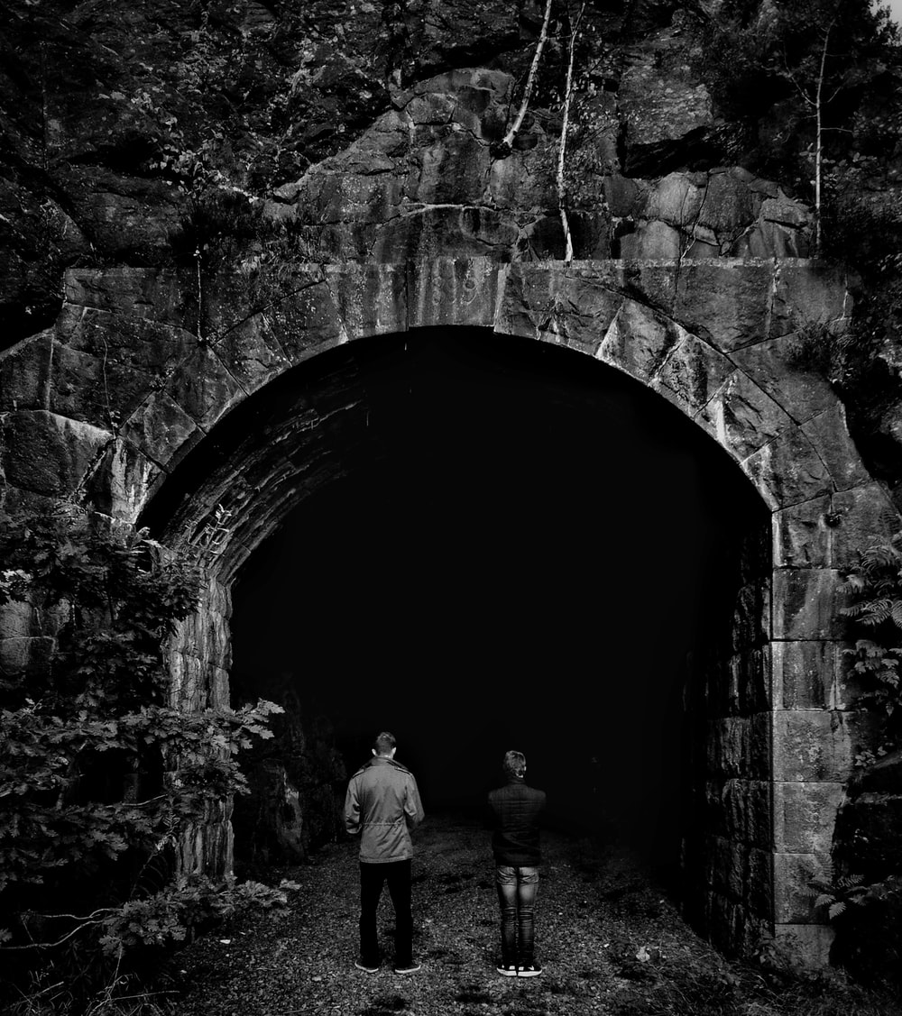 grayscale photo of two person facing tunnel