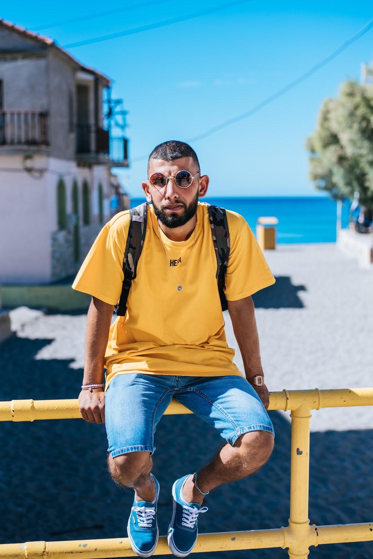 man in yellow T-shirt sitting on metal bar