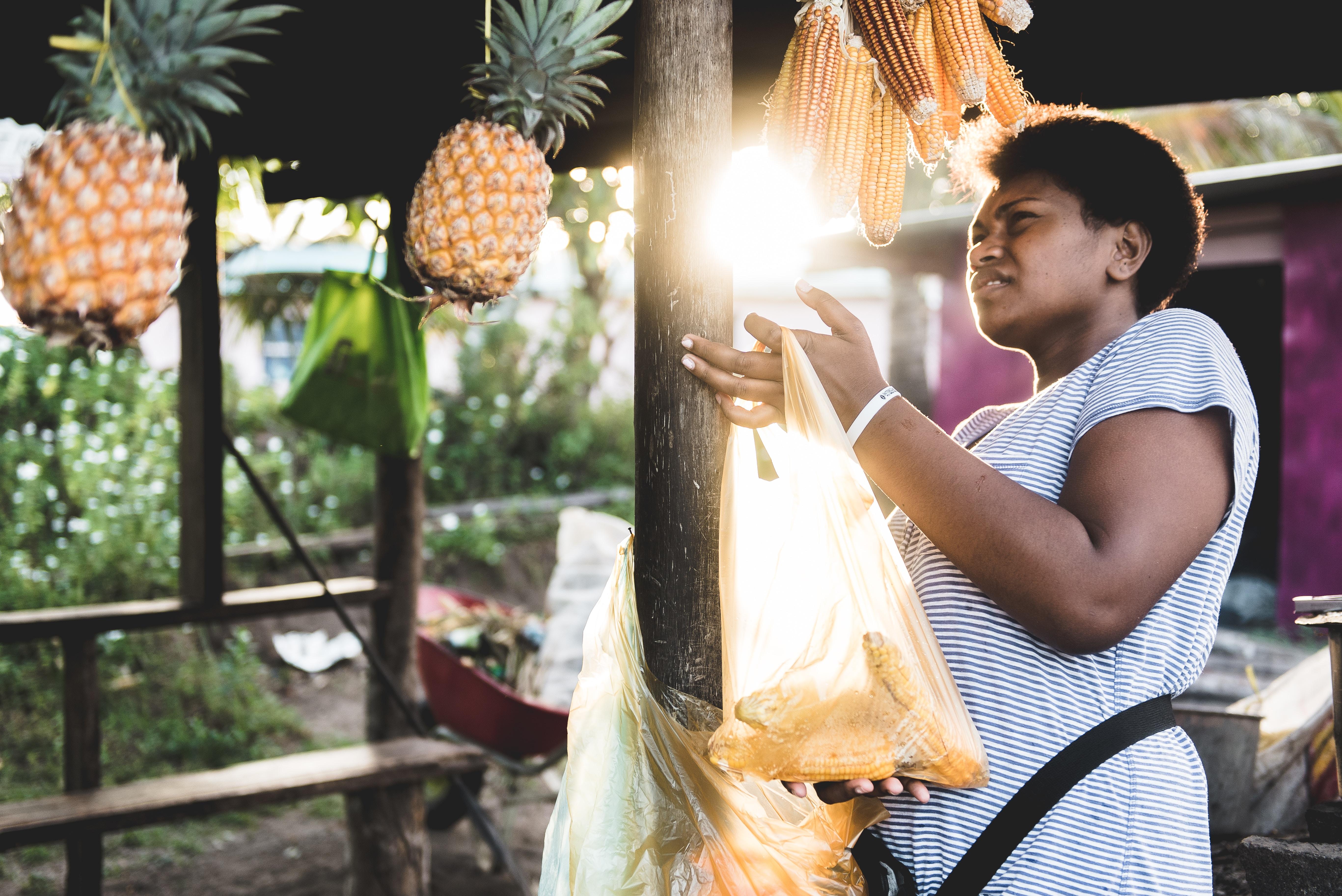 woman holding yellow plastic bag near pineapple fruits