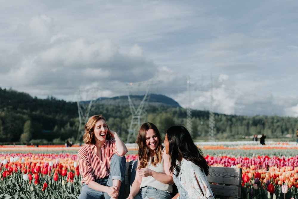 3 women sitting on bench near the flowers