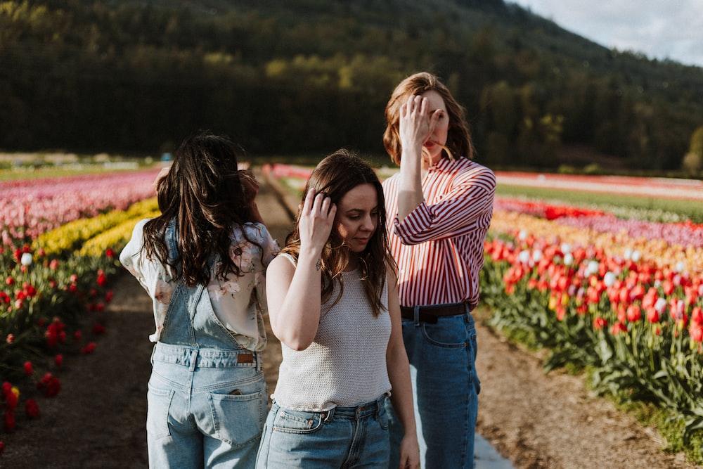 three women standing between flower garden