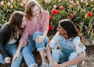 three woman sitting near the flower
