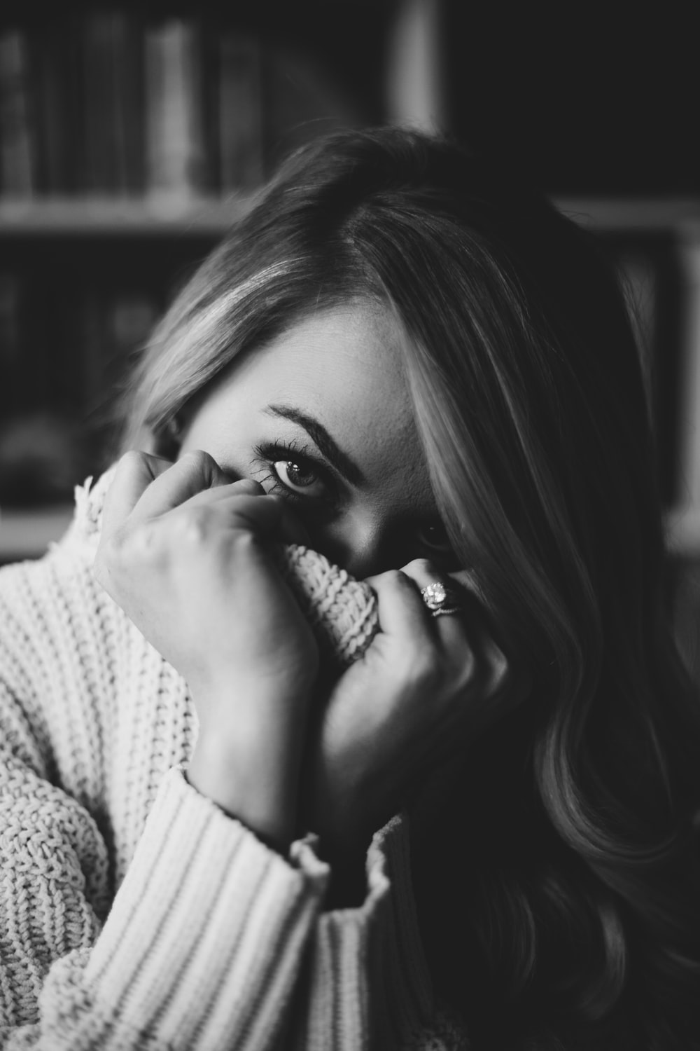 grayscale photography of woman covering face using sweater