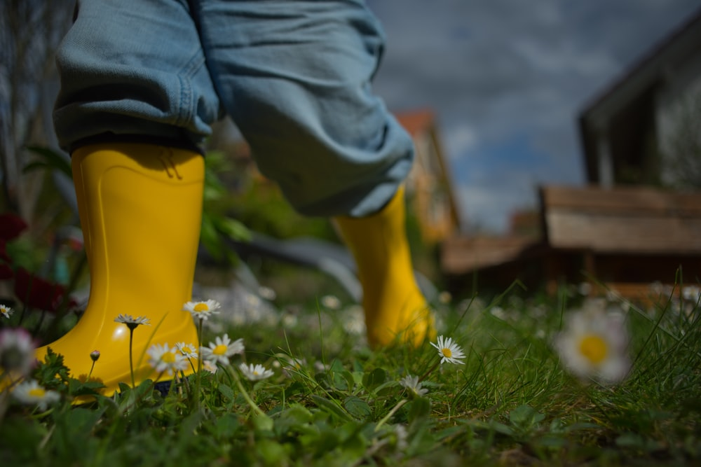 person wearing yellow rain boots during daytime