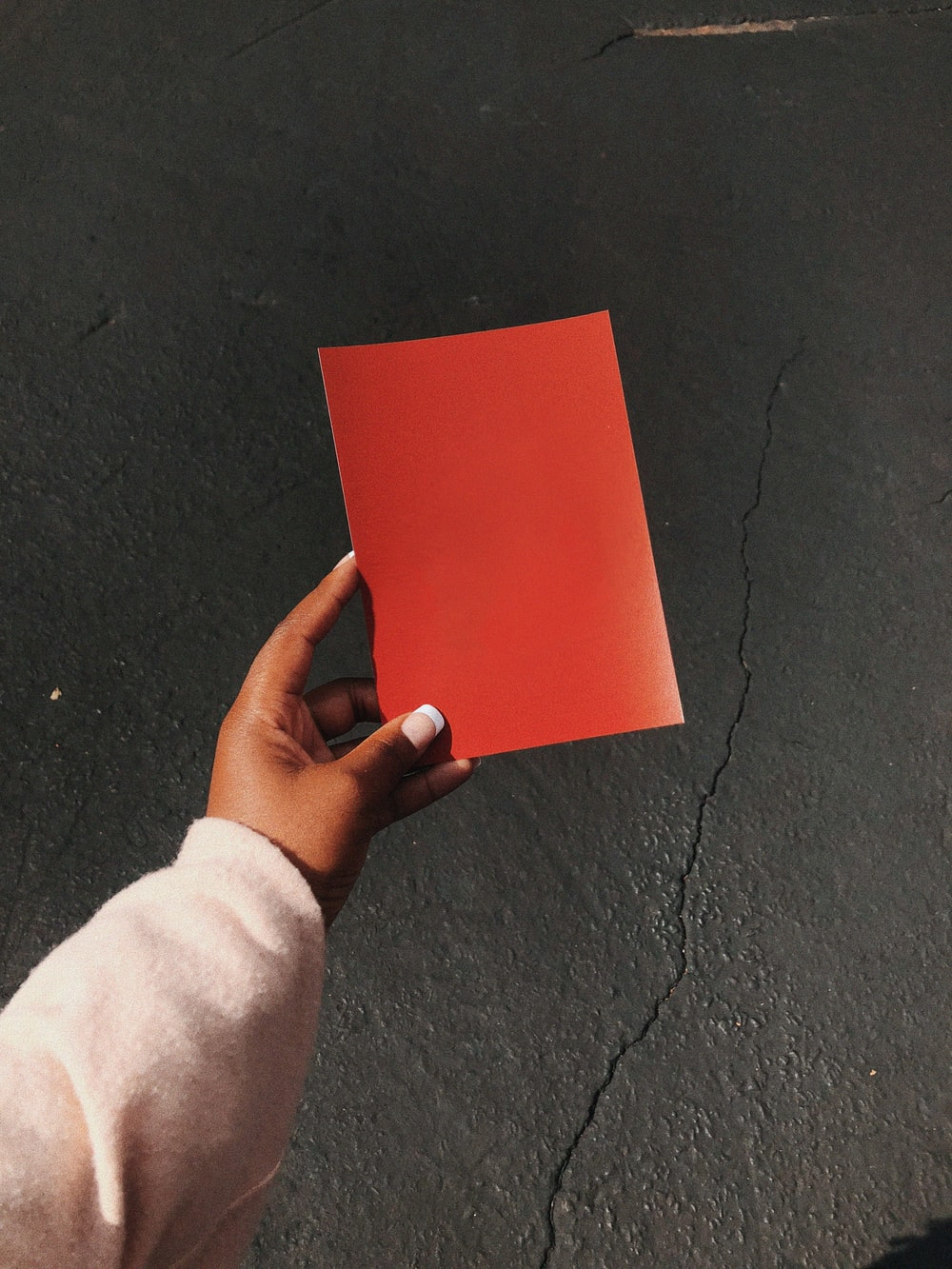 person holding red paper