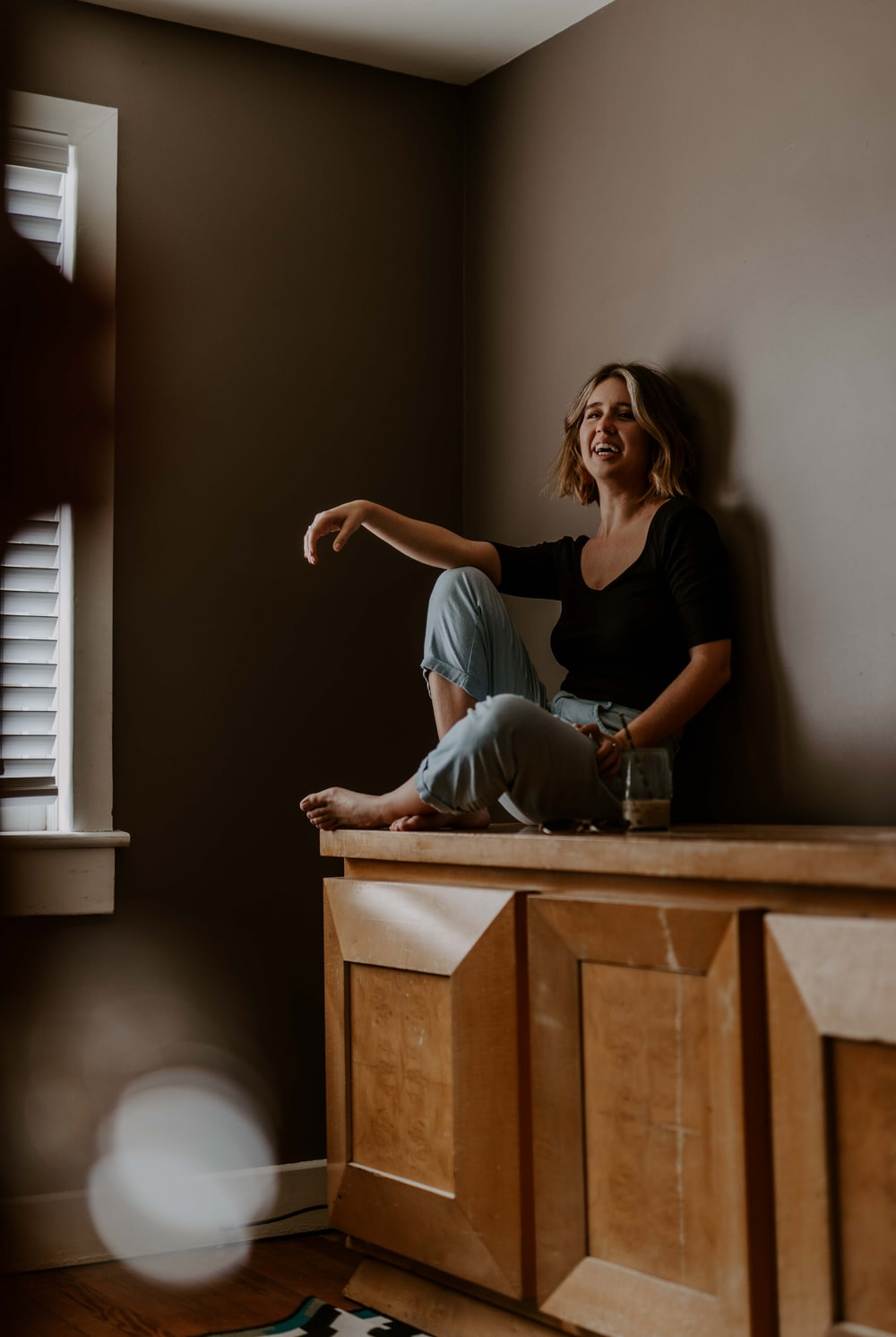 woman sitting on wooden sideboard against wall