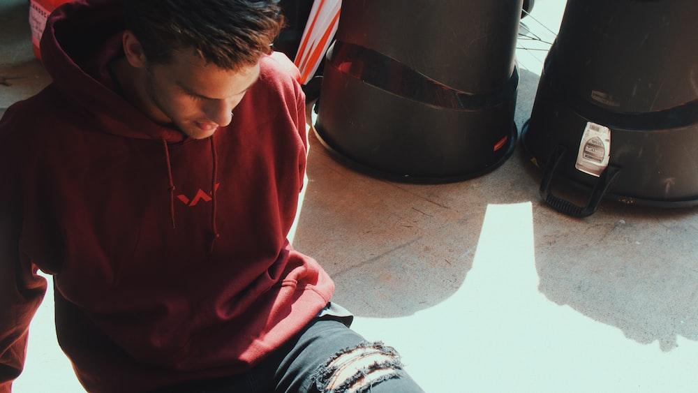 man in red drawstring hoodie sitting on ground