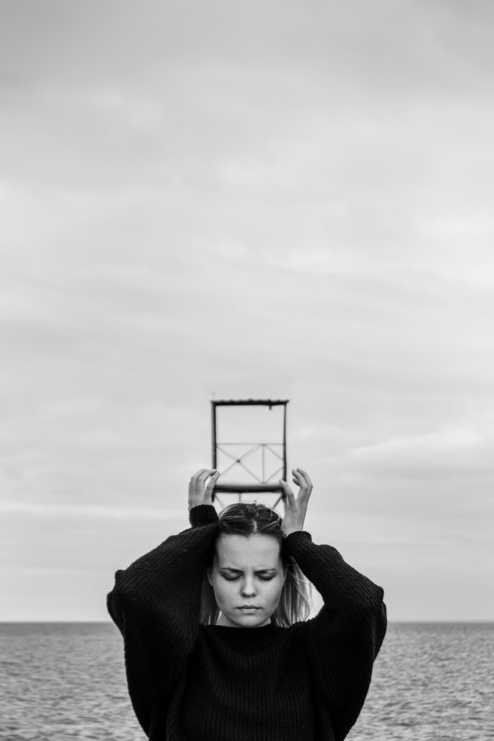 grayscale photography of woman holding square metal frame over her head