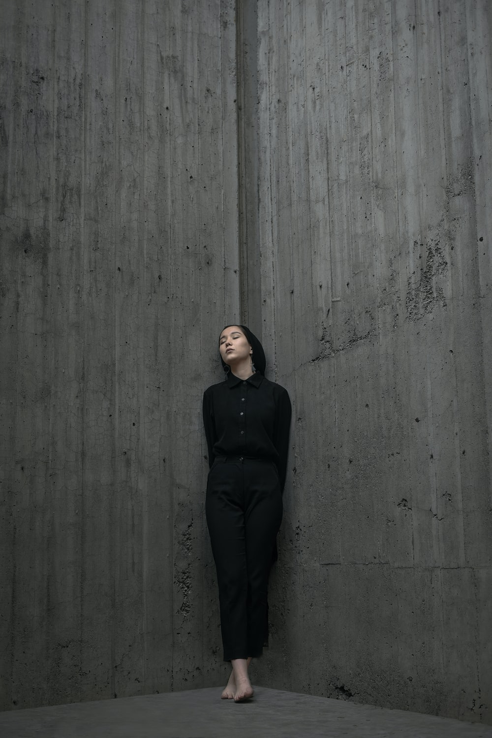 woman standing and leaning on concrete wall corner