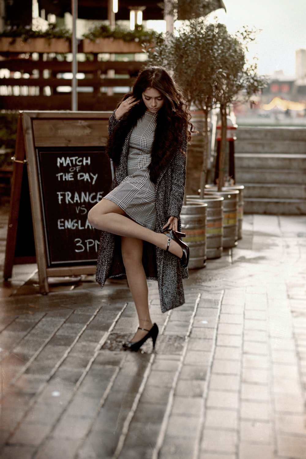 woman touching her left heel wearing stiletto shoes