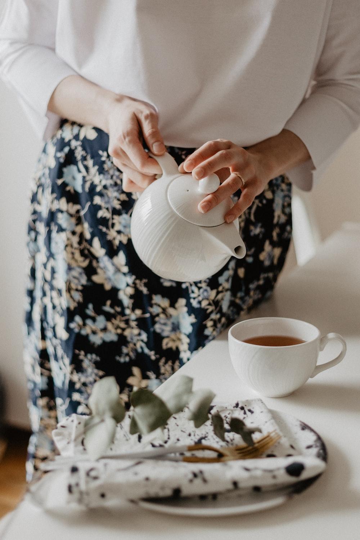 woman holding teapot pouring on coffee mug on table