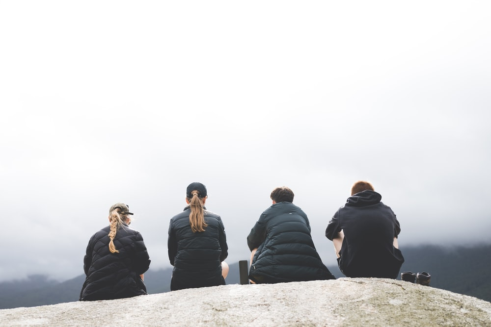 four persons sitting on gray rock