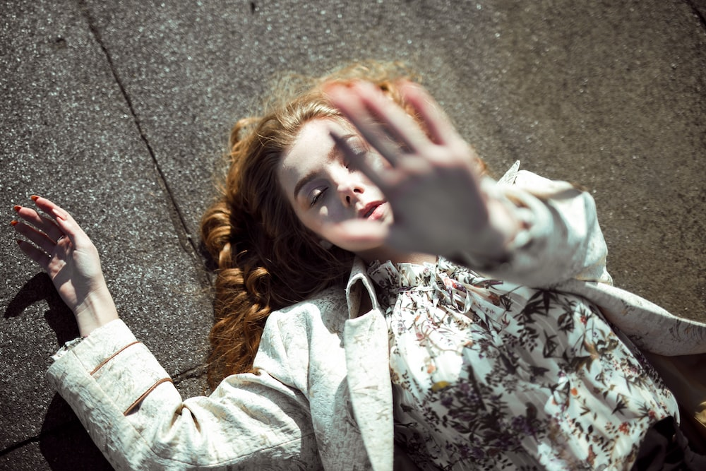 woman lying on concrete pavement and raising her left hand
