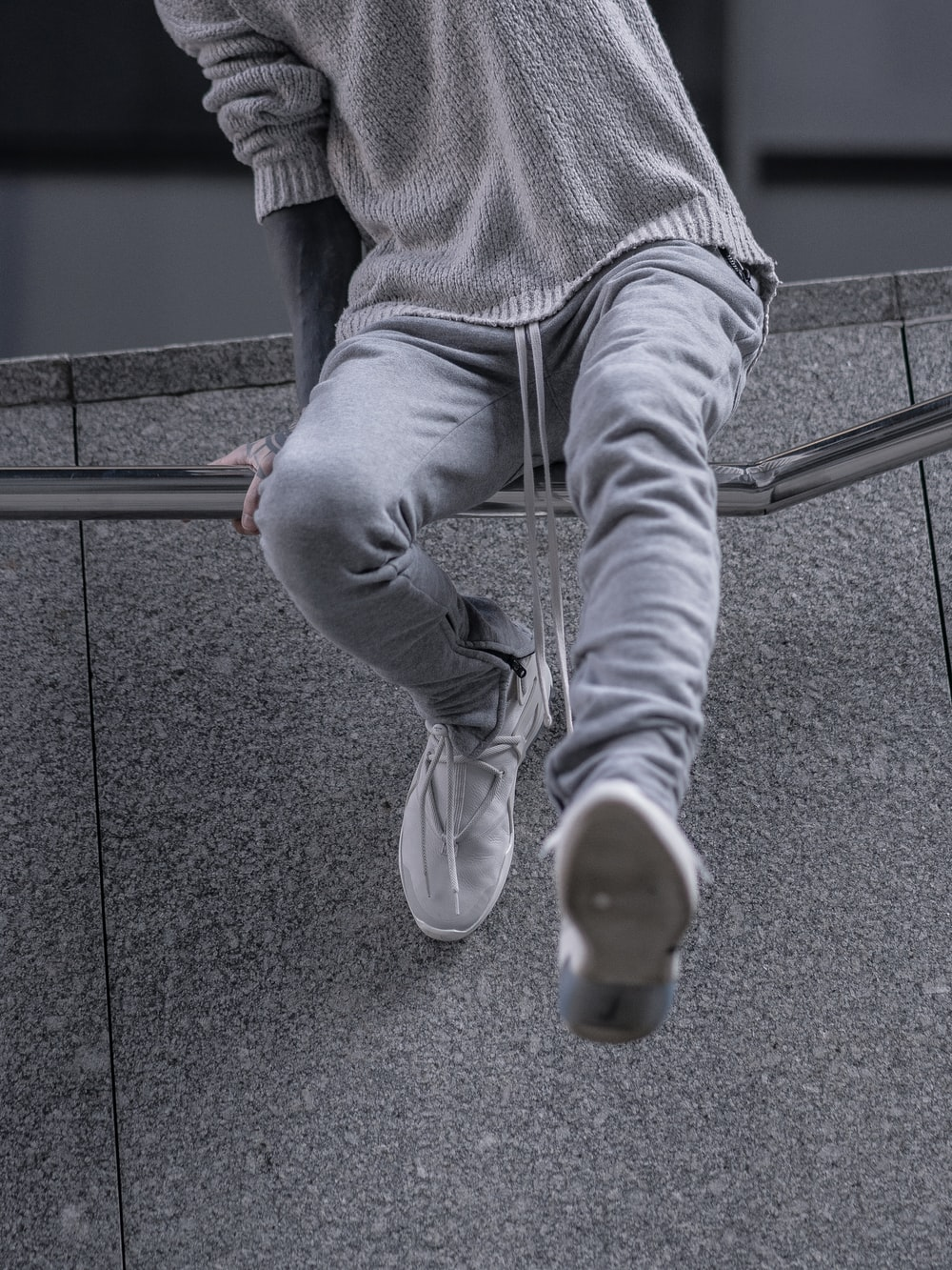 person wearing gray track pants and gray long-sleeved shirt mid air jump