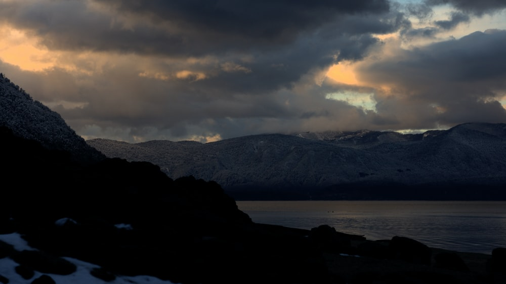silhouette of mountain near sea during golden hour