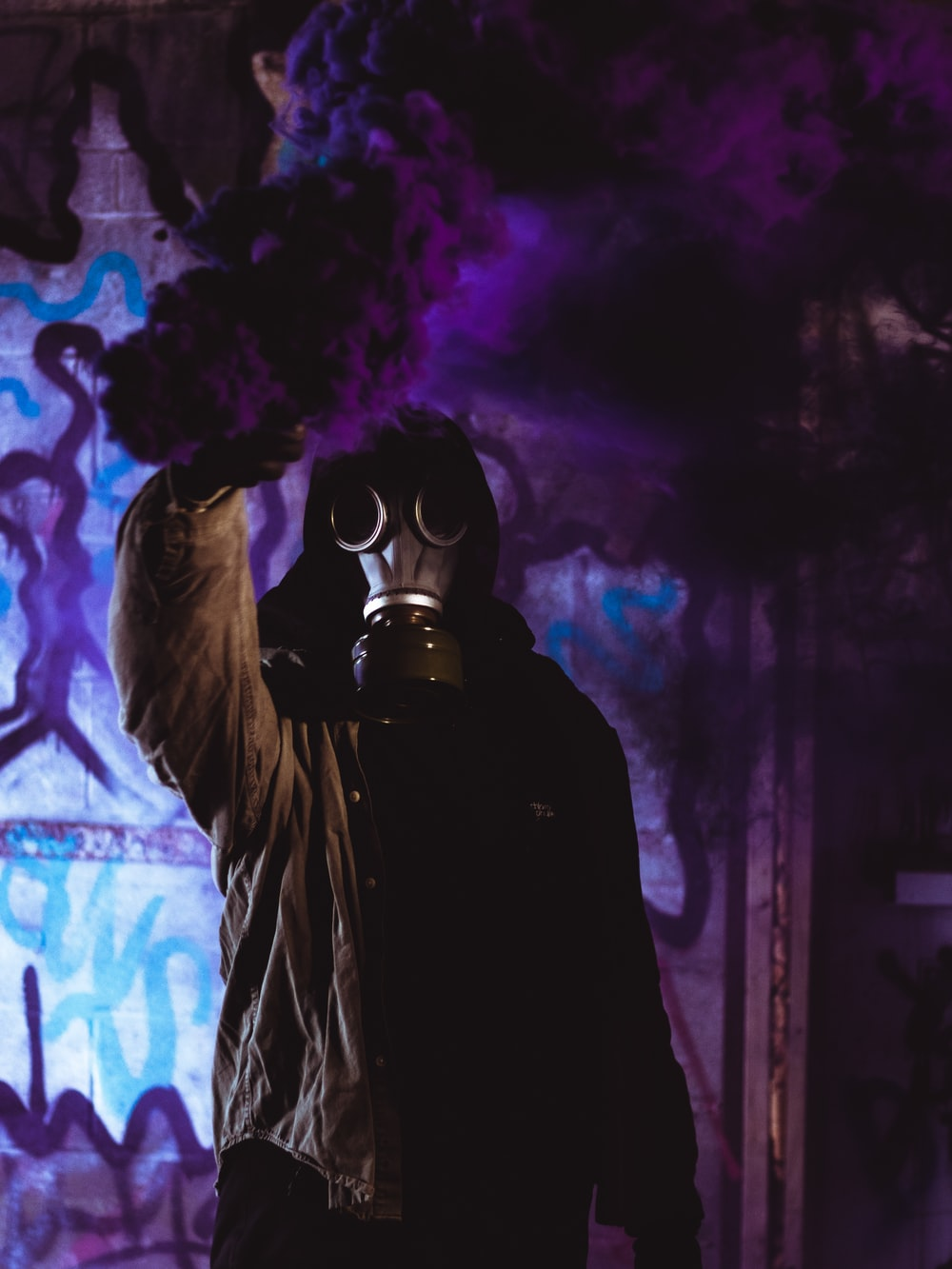 person wearing mask holding paint pray