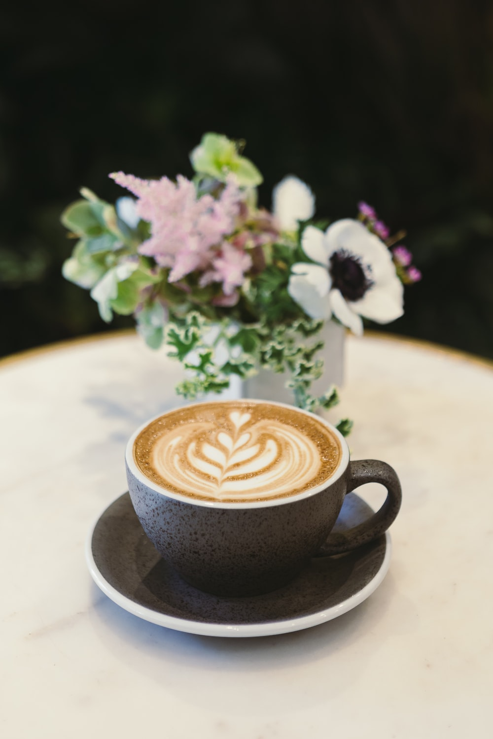cup of cappuccino on saucer beside flower centerpiece