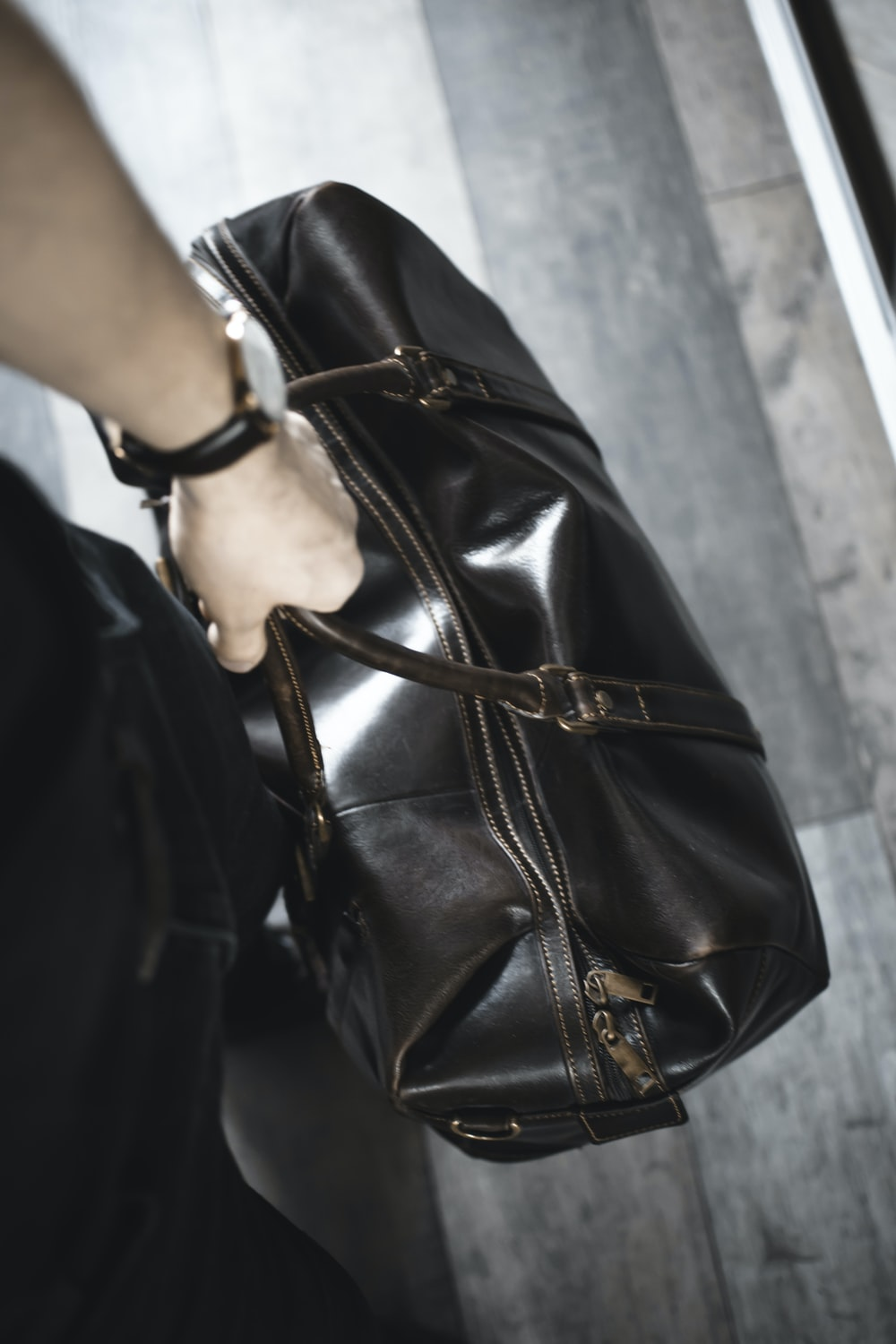 person holding brown leather handbag