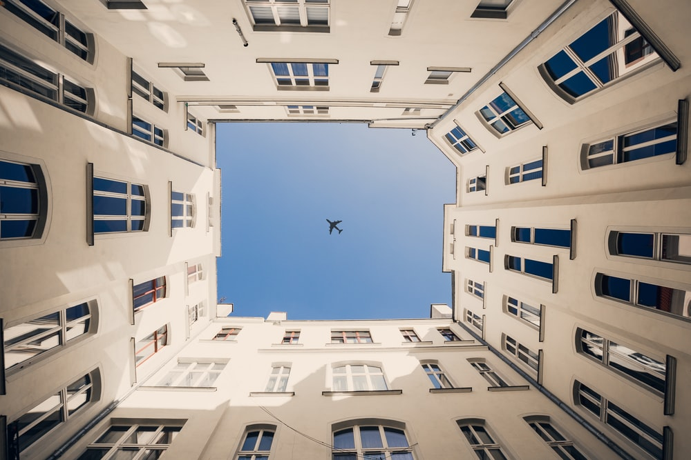 plane above white building