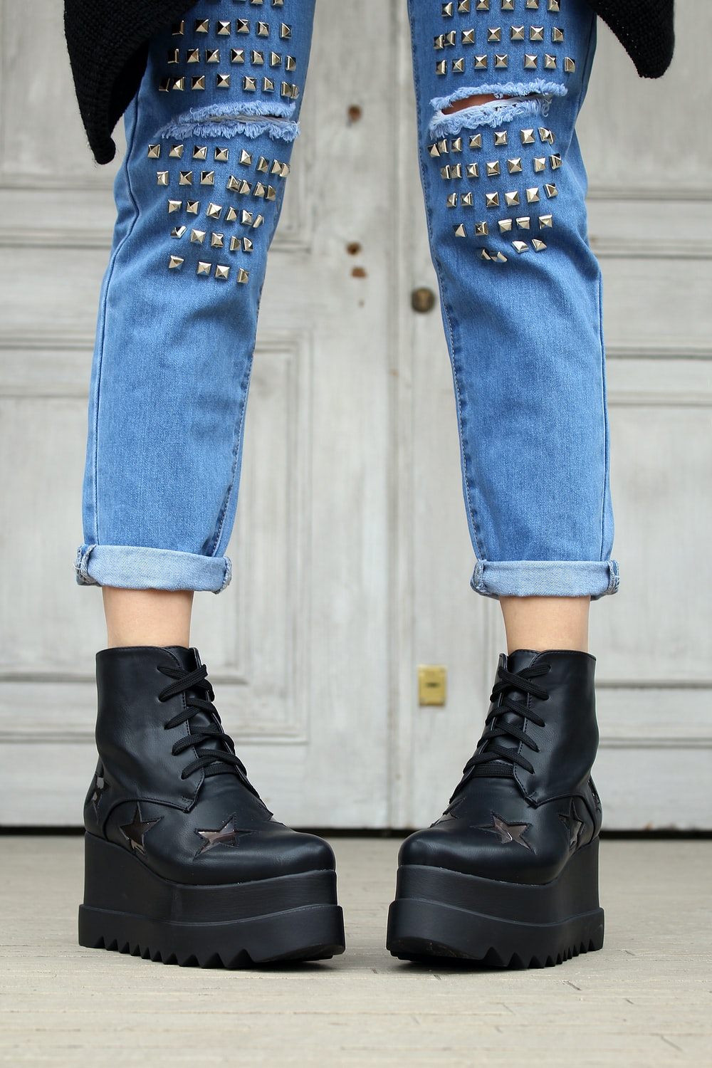 person in blue denim distressed jeans and black platform boots