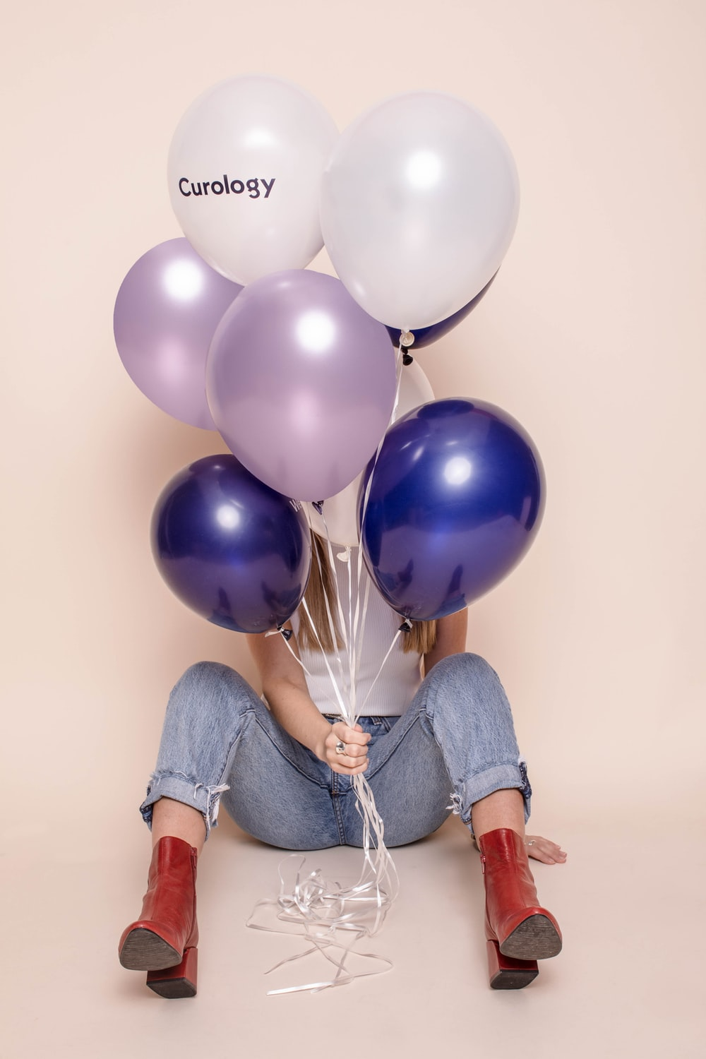 woman holding six assorted-color balloons