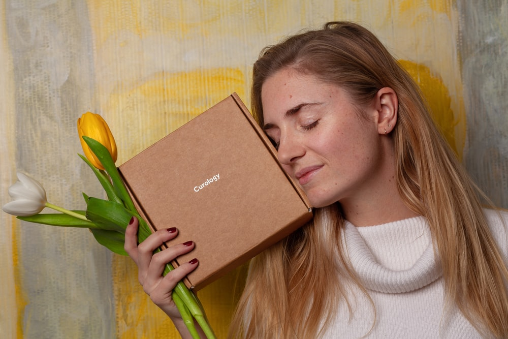 woman in white sweater holding brown box and tulip flowers