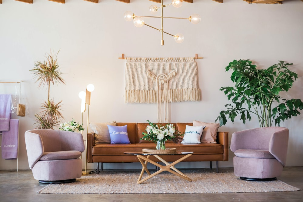 brown leather sofa and two pink sofa chair