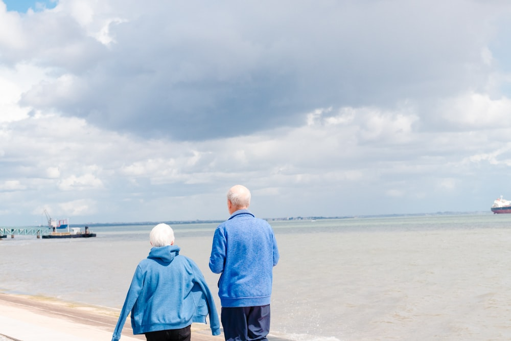 man and woman in blue jackets walking in front of body of water