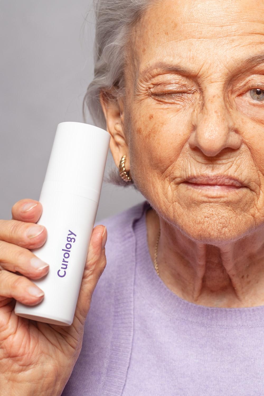 woman holding Curology bottle