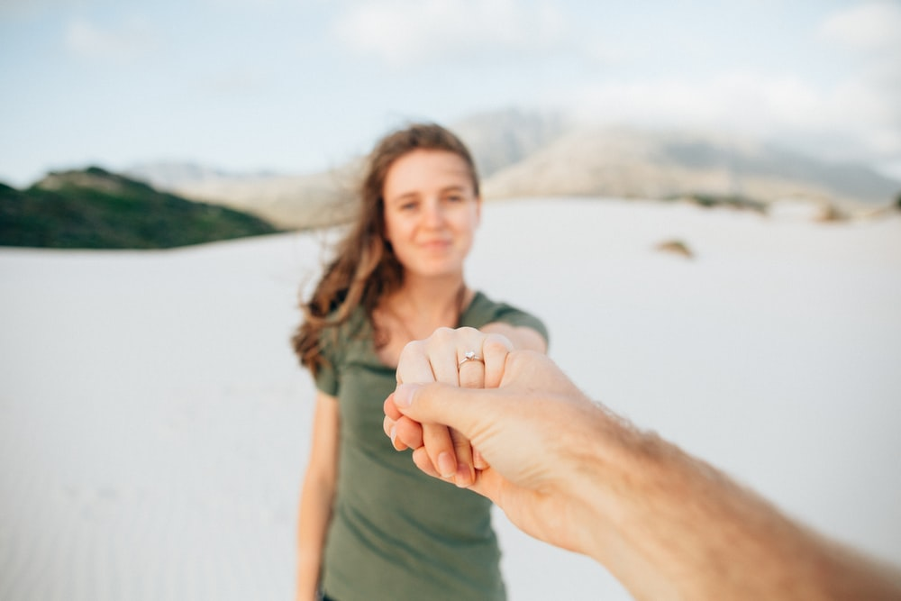 woman wearing green top holding hand