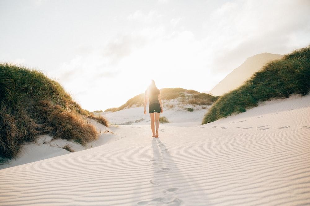 woman walking on beach sand