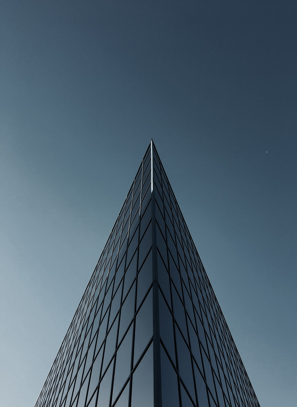 low angle photography of glass building under clear sky