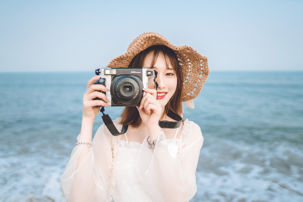 woman holding camera at the beach
