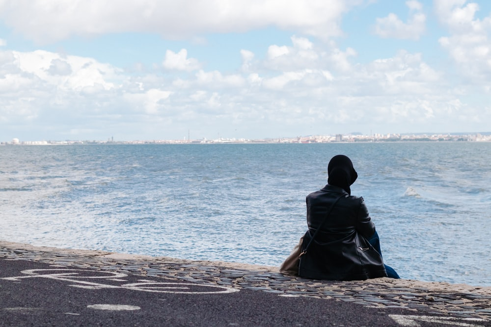 person sitting on concrete seawall