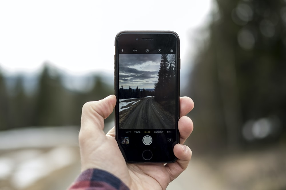selective focus photography of iPhone taking photo