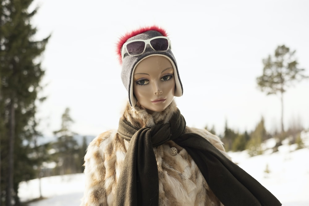 woman in beige coat and white glasses Barbie doll