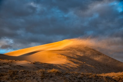 Wind at sunset creates blowing sand at the Kelso Dunes in Mojave National Preserve, California.