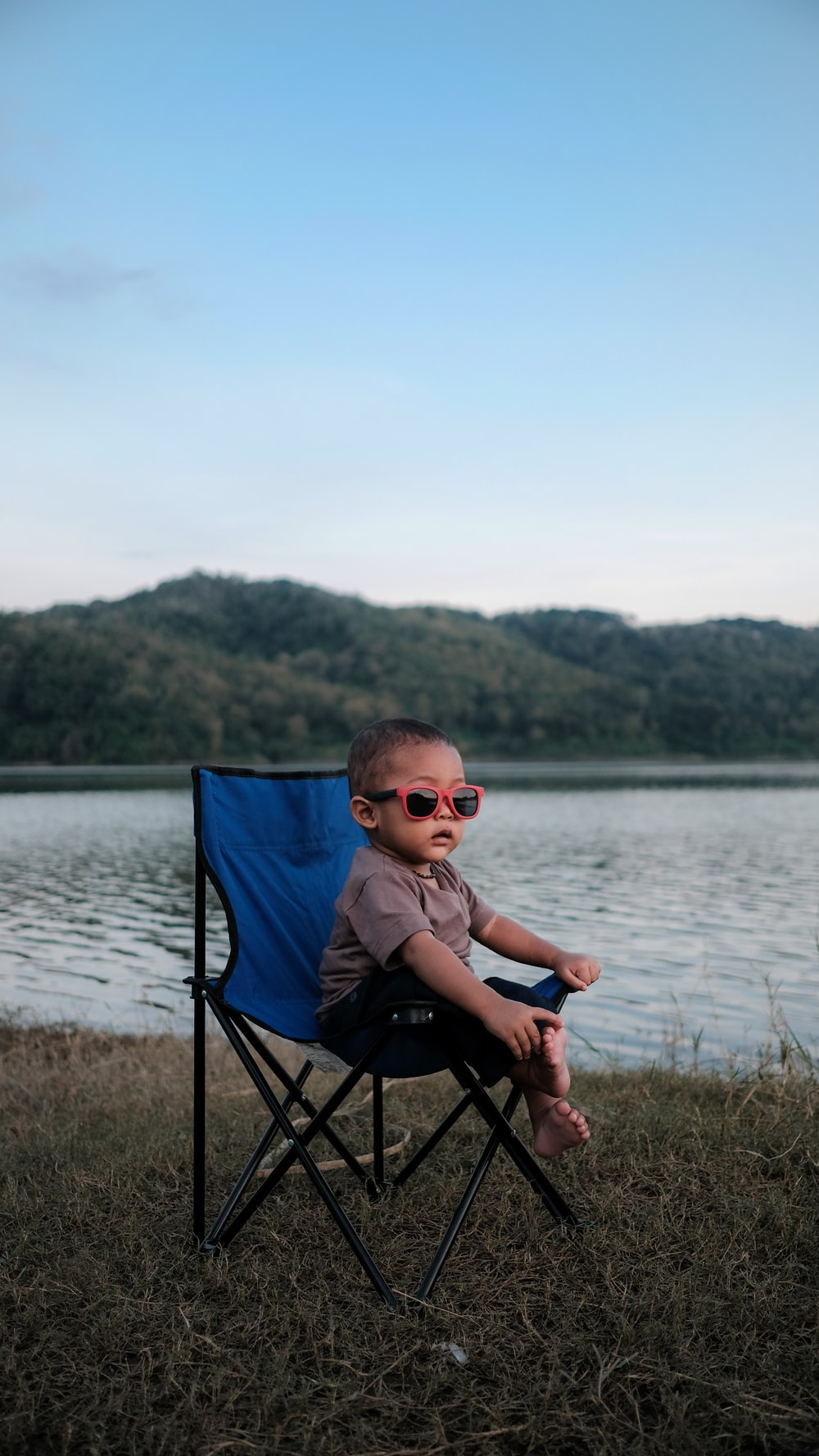 boy in gray shirt sitting on blue camping chair near body of water