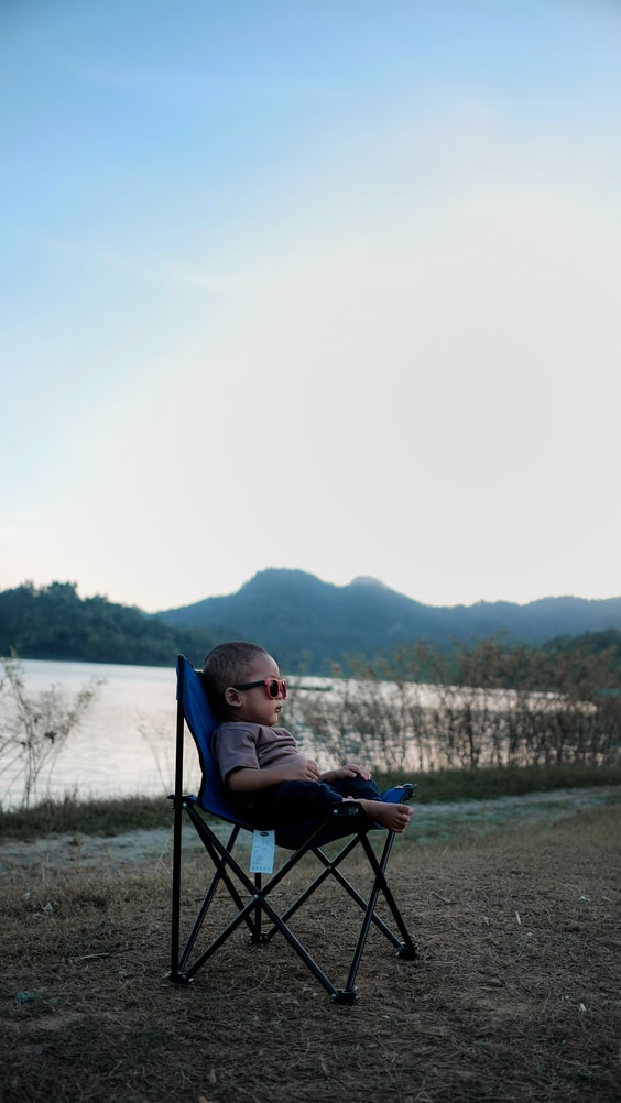 A picture of a baby sitting in a camping chair wearing sunglasses and looking like a middle-aged man, relaxed on vacation.