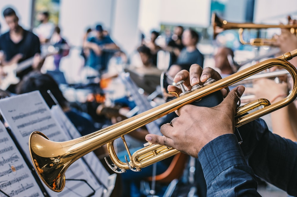 person playing gold trumpet