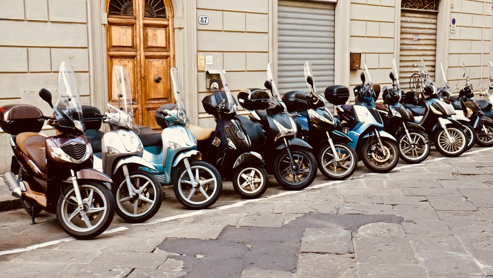 motor scooter lined parking area during daytime