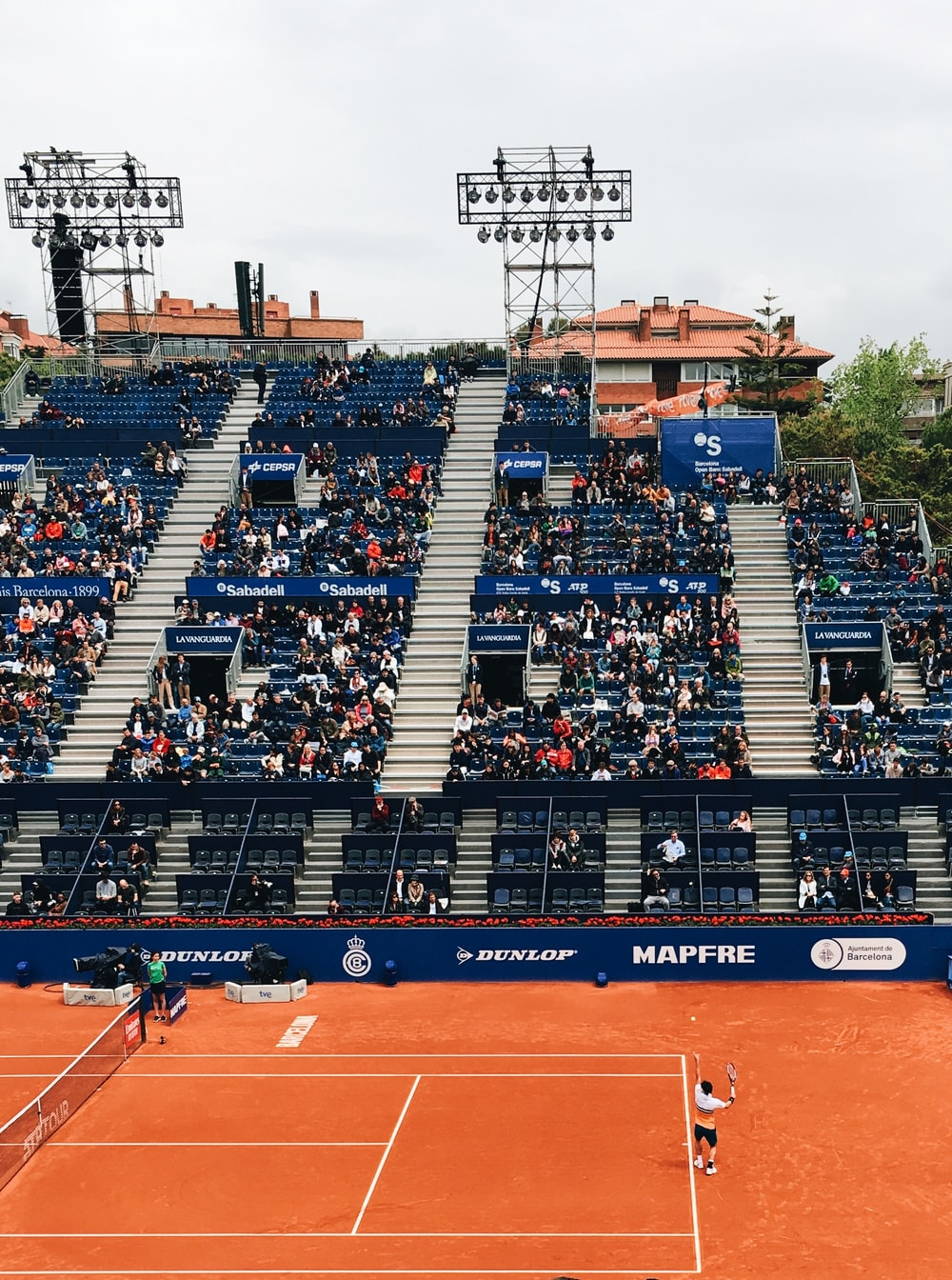 people sitting on bleachers while watching lawn tennis game during daytime