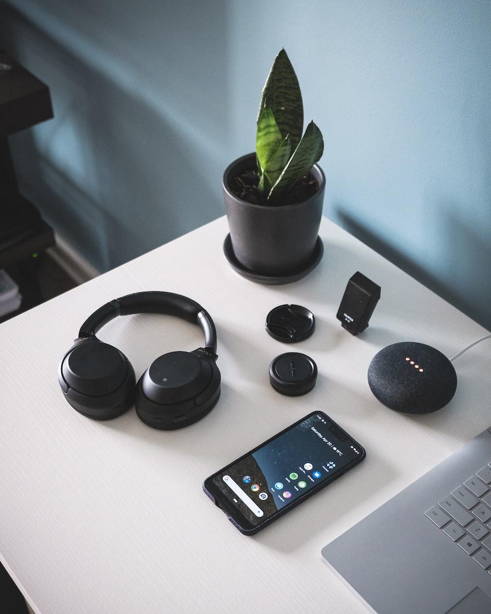 smartphone beside headphones and Google Home Mini