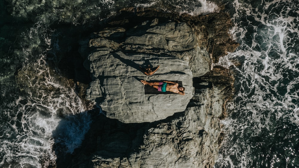 person lying on grey rock during daytime