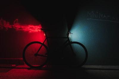 暗闇に赤と青で照らされた自転車の画像
